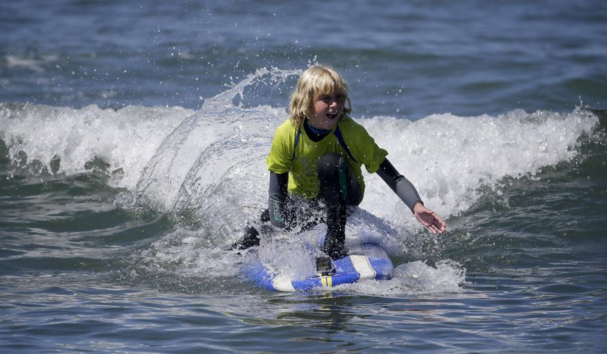 Michael Montelone, 10, rides a wave Thursday, July 24, 2014, in San Clemente, Calif. Three of the Montelone's five children who have  cystic fibrosis are part of a growing number of people to take advantage of the health benefits that come with surfing. (AP Photo/Chris Carlson)