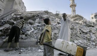 A Palestinian man talks to a boy carrying containers as they stand amid the rubble of al-Qassam mosque, hit by an Israeli airstrike. Hamas officials said they were holding out in hopes of getting more concessions in the curretn Egyptian-mediated talks. (AP Photo/Adel Hana)