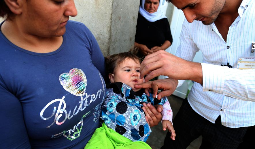 An Iraqi internally displaced Yazidi child receives a polio vaccine at the town of Khanke, outside Dahuk, 260 miles (430 kilometers) northwest of Baghdad on Sunday, Aug. 17, 2014. The Yazidis are a centuries-old religious minority viewed as apostates by the Islamic State group, which has claimed mass killings of its opponents in Syria and Iraq. Tens of thousands of Yazidis fled earlier this month when the Islamic State group captured the town of Sinjar, near the Syrian border. (AP Photo/Khalid Mohammed)