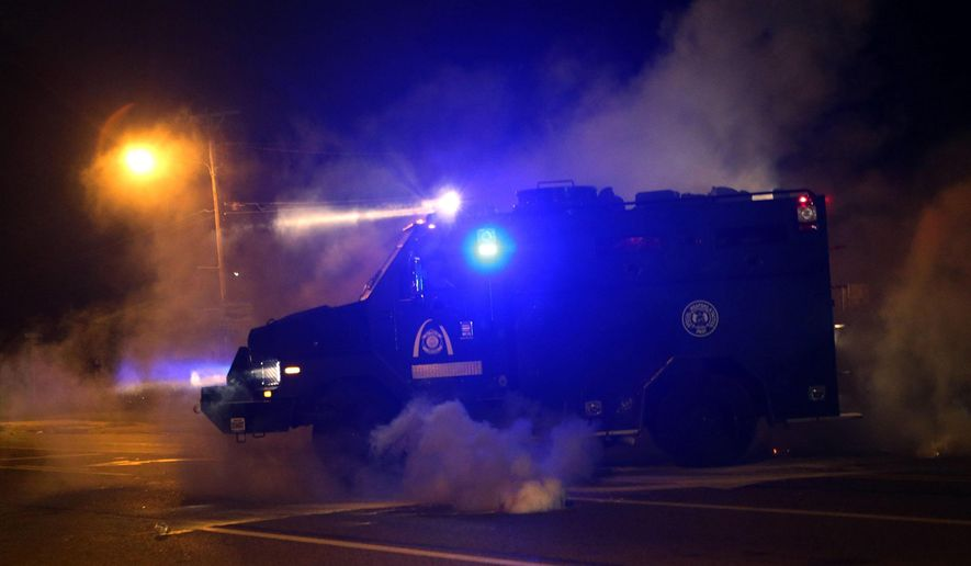 A tactical trucks moves down the street through tear gas in Ferguson, Mo., Sunday, Aug. 17, 2014. Protests over the killing of 18-year-old Michael Brown by a white police officer have entered their second week. (AP Photo/St. Louis Post-Dispatch, J.B. Forbes)