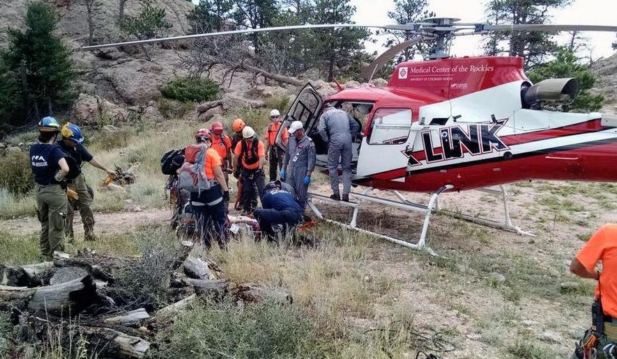 In this photo provided by the Poudre Fire Authority, search and rescue teams prepare to load a rescued hiker onto a medical evacuation helicopter Monday, Aug. 18, 2014, after a 16-year-old hiker fell and spent about three hours in a crevice near a popular hiking trail in northern Colorado. More than 40 people worked to pull the girl from the crevice on Horsetooth Rock in the Horsetooth Mountain Open Space on Monday. (AP Photo/Poudre Fire Authority)