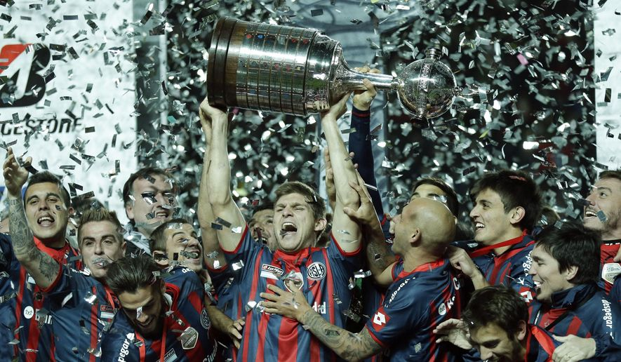 In this Aug. 13, 2014 photo, Walter Kannemann of Argentina's San Lorenzo, center, lifts the trophy after San Lorenzo won the 2014 Copa Libertadores championship against Paraguay's Nacional during the Copa Libertadores final soccer match in Buenos Aires, Argentina. The Argentine team, Pope Francis' favorite, defeated Nacional 2-1 on aggregate to win the title for the first time. (AP Photo/Victor R. Caivano)