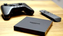This April 2, 2014 image provided by Amazon shows the Amazon Fire TV system during a news conference in New York. Apple and Amazon have ways to encourage you to buy more of their products: Offer bonus features that work only with gadgets from the same company. (Photo by Diane Bondareff/Invision for Amazon/AP Images, File)