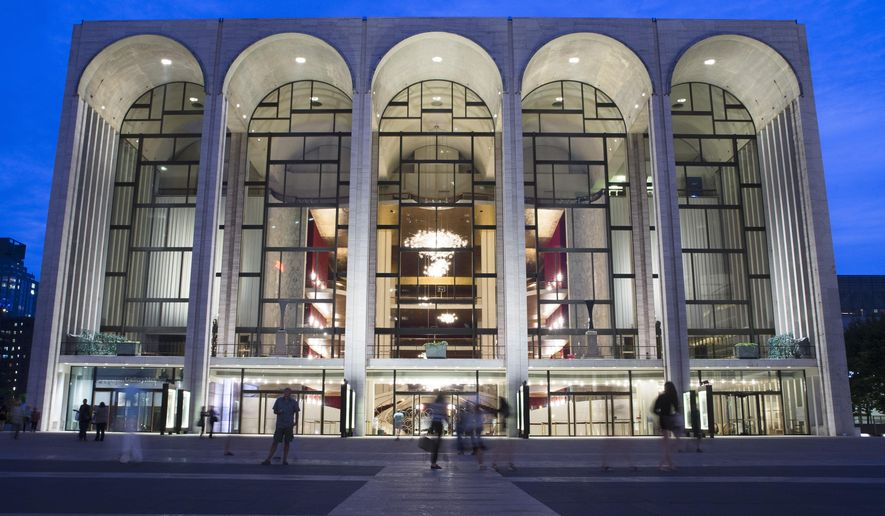 FILE - In this Aug. 1, 2014, file photo, pedestrians walk in front of the Metropolitan Opera house at New York's Lincoln Center. New York's Metropolitan Opera has reached tentative labor deals with two of its largest unions while negotiations continue with 10 more unions in hopes of averting a lockout, the federal Mediation and Conciliation Service announced early Monday, Aug. 18, 2014. (AP Photo/John Minchillo, File)