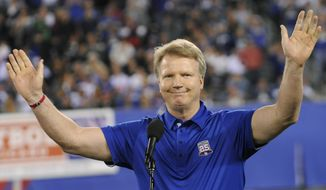Former New York Giants quarterback Phil Simms waves to the fans during halftime of an NFL football game against the St. Louis Rams Monday, Sept. 19, 2011, in East Rutherford, N.J. (AP Photo/Bill Kostroun)