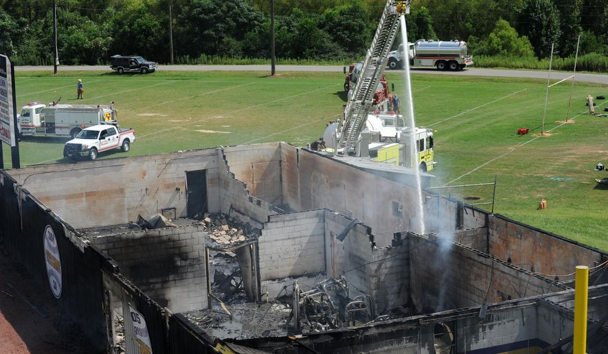 Firefighters use a ladder truck to extinguish hot spots after a fire destroyed the Purvis High School field house Saturday, Aug. 16, 2014, in Purvis, Miss. (AP Photo/The Hattiesburg American, Kelly Price)  NO SALES