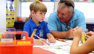 Grayson Murphy, 5, of Pink Hill, N.C., left, listens to his father Hal, right, as he settles into kindergarten on the first day of school Monday, Aug. 18, 2014, at Arendell Parrott Academy in Kinston, N.C. (AP Photo/Daily Free Press, Janet S. Carter)