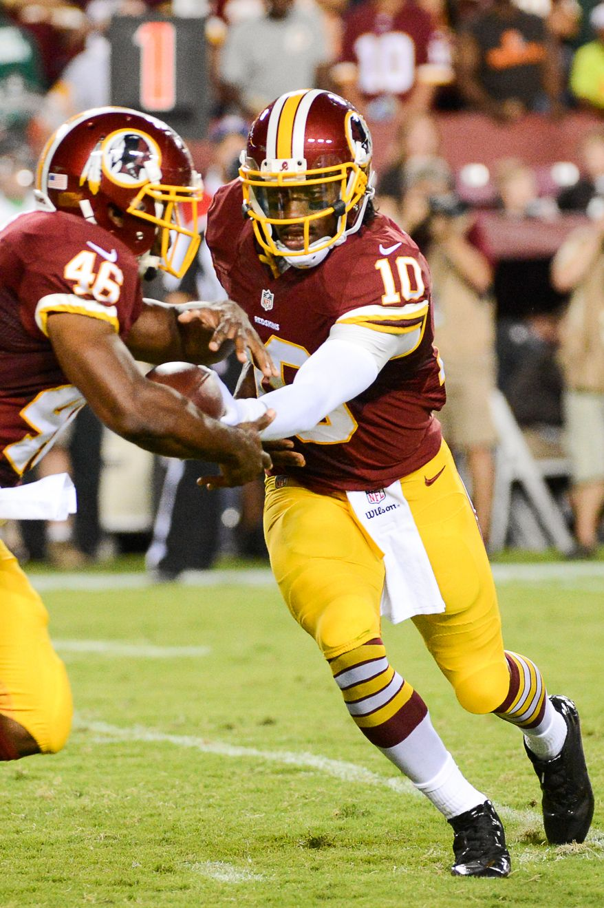 Washington Redskins quarterback Robert Griffin III (10) hands off to Washington Redskins running back Alfred Morris (46) in the first quarter as the Washington Redskins play the Cleveland Browns in NFL preseason football at FedExField, Landover, Md., Monday, August 18, 2014. (Andrew Harnik/The Washington Times)