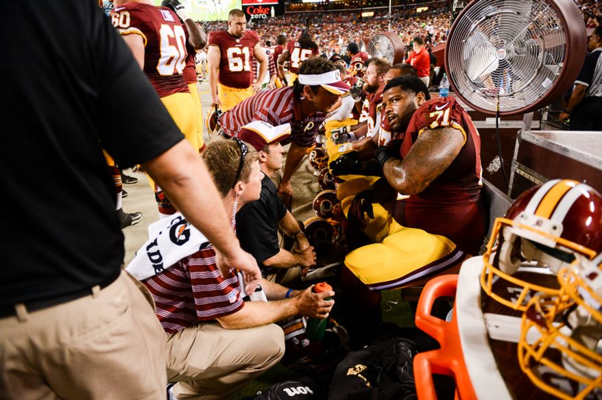 Washington Redskins tackle Trent Williams (71) is looked at by team medical personnel in the first quarter as the Washington Redskins play the Cleveland Browns in NFL preseason football at FedExField, Landover, Md., Monday, August 18, 2014. (Andrew Harnik/The Washington Times)