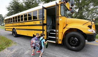 Cash Keeler 5, left and Riley Myers 5 board their bus to take them to their 1st day of kindergarten at Gainesboro Elementary School near Winchester, Va. on Monday, Aug. 18, 2014. Monday was the first day students reported to Frederick County, Va. Public Schools for the 2014-2015 year. (AP Photo/The Winchester Star, Ginger Perry)