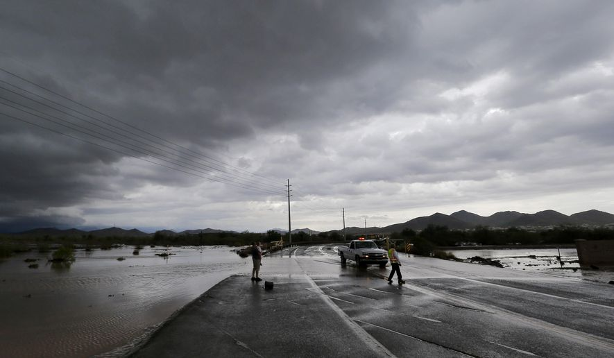 A city of Phoenix official blocks a closed section of road as flash flood waters overrun Skunk Creek through the Sonoran Desert, Tuesday, Aug. 19, 2014, in northwestern Phoenix. Flooding from heavy rain in the Phoenix area has forced authorities to close several major roads, including a portion of Interstate 17 about 25 miles north of the city. (AP Photo/Matt York)