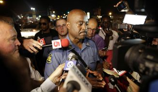 Capt. Ron Johnson of the Missouri Highway Patrol is surrounded by media after meeting with protesters Monday, Aug. 18, 2014, in Ferguson, Mo. The Aug. 9 shooting of Michael Brown by a police officer has touched off rancorous protests in Ferguson, a St. Louis suburb where police have used riot gear and tear gas. (AP Photo/Jeff Roberson)