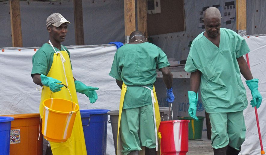 Health workers with buckets, as part of their Ebola virus prevention protective gear, at an Ebola treatment center in the city of Monrovia, Liberia, Monday, Aug. 18, 2014. Liberia's armed forces were given orders to shoot people trying to illegally cross the border from neighboring Sierra Leone, which is closed to stem the spread of Ebola, local newspaper Daily Observer reported Monday. (AP Photo/Abbas Dulleh)