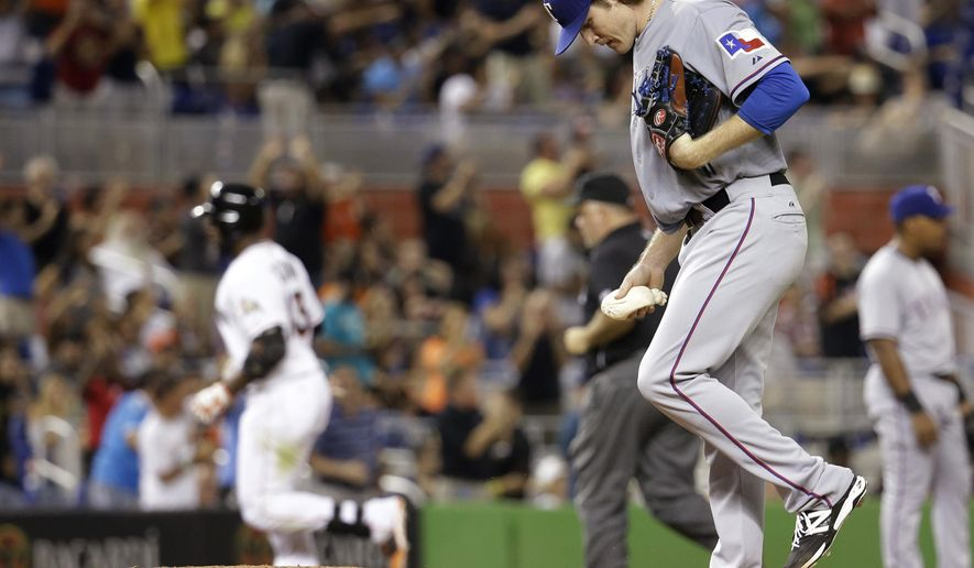 Texas Rangers starting pitcher Miles Mikolas right, kicks the mound as Miami Marlins' Marcell Ozuna, left, rounds third base after hitting a solo home run in the fourth inning during a baseball game, Tuesday, Aug. 19, 2014, in Miami. (AP Photo/Lynne Sladky)