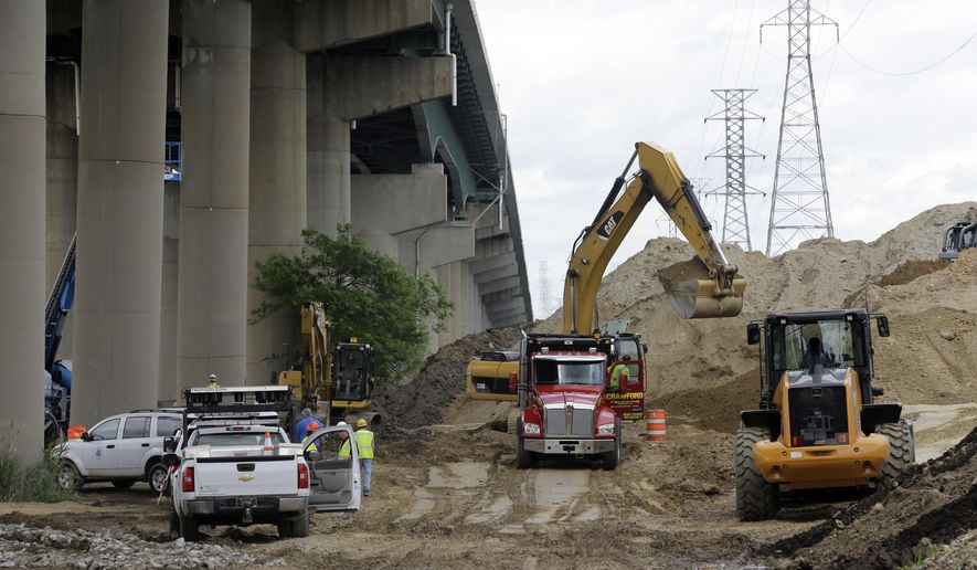FILE -In this Thursday, June 5, 2014 file photo, workers remove a pile of dirt next to the Interstate 495 bridge over the Christina River near Wilmington, Del. The owners of land in Delaware where a huge mound of dirt caused damage to an interstate highway bridge on a key East Coast artery have been served with violation notices by state environmental regulators in August 2014. (AP Photo/Patrick Semansky, File)