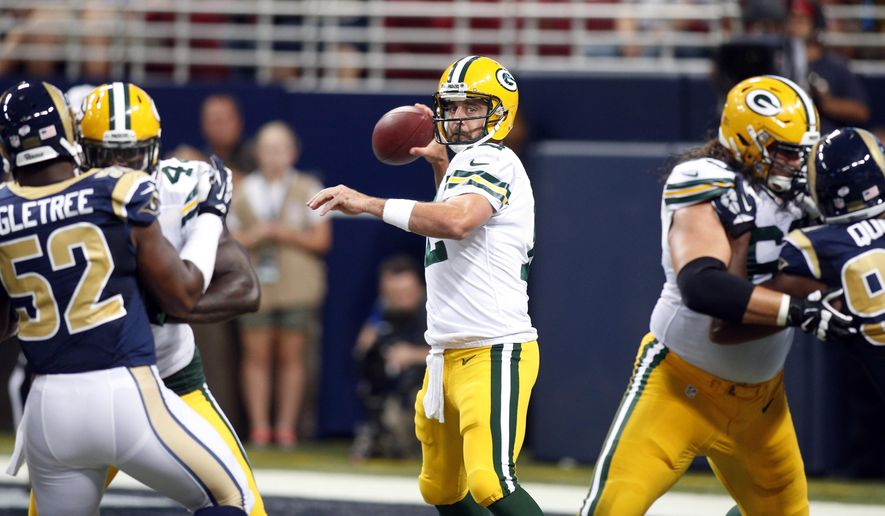Green Bay Packers quarterback Aaron Rodgers, center, throws during the first quarter of an NFL preseason football game against the St. Louis Rams, Saturday, Aug. 16, 2014, in St. Louis. (AP Photo/Scott Kane)