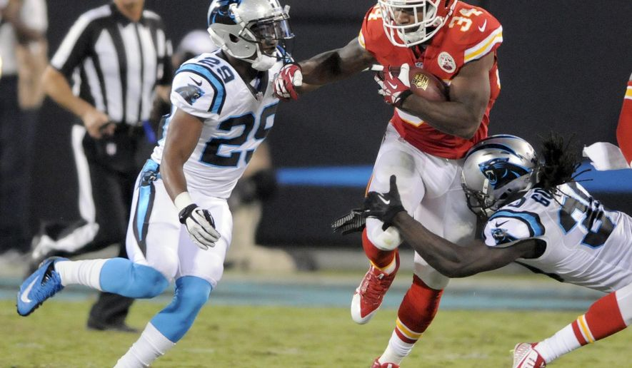 Kansas City Chiefs' Knile Davis (34) runs through the tackle of Carolina Panthers' Charles Godfrey (30) and Bene Benwikere (29) during the first half of a preseason NFL football game in Charlotte, N.C., Sunday, Aug. 17, 2014. (AP Photo/Mike McCarn)