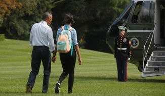 President Obama walks with his daughter Malia on the South Lawn as he returns to Martha's Vineyard to continue his vacation. (Associated Press)