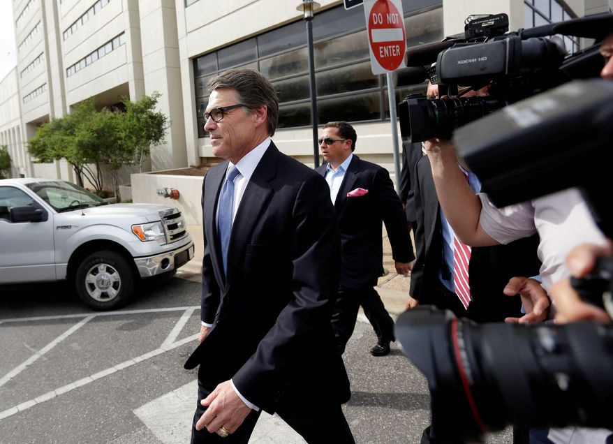Texas Gov. Rick Perry leaves the Blackwell Thurman Criminal Justice Center after he was booked in Austin Tuesday. Mr. Perry was indicted last week on charges of coercion and official oppression for publicly promising to veto $7.5 million for the state's public integrity unit unless the head of the unit, a district attorney convicted of drunken driving, resigned. (Associated Press)