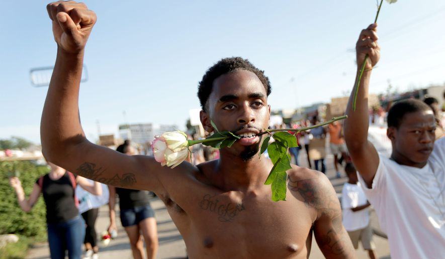 "Protesters march on Tuesday for 18-year-old Michael Brown, who was killed by police Aug. 9 in Ferguson, Missouri. Ferguson's leaders urged residents Tuesday to stay home after dark to ""allow peace to settle in"" and pledged several actions to reconnect with the predominantly black community in the St. Louis suburb. (Associated Press)"