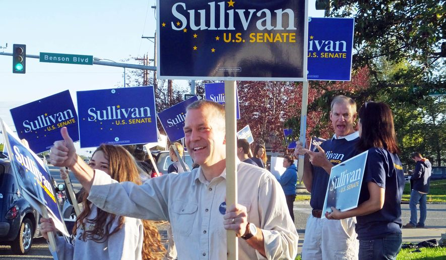 Dan Sullivan, candidate for the Republican candidate for election to the U.S. Senate, waves signs along a busy street on the morning of Alaska's primary election Tuesday, Aug. 19, 2014, in Anchorage, Alaska. (AP Photo/Becky Bohrer)