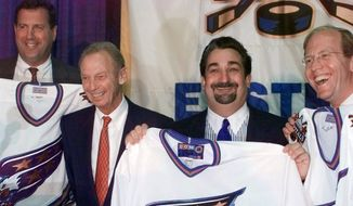**FILE** Ted Leonsis, second from right, Jon Ledecky, right, and Dick Patrick, left, hold up Washington Capitals jerseys at a news conference Wednesday, May 12, 1999, at the MCI Center in Washington. Wednesday, May 12, 1999, at the MCI Center in Washington Leonsis heads an investment group, including Patrick and Ledecky, which purchased the Washington Capitals NHL team from Abe Pollin, second from left, (AP Photo/Nick Wass)