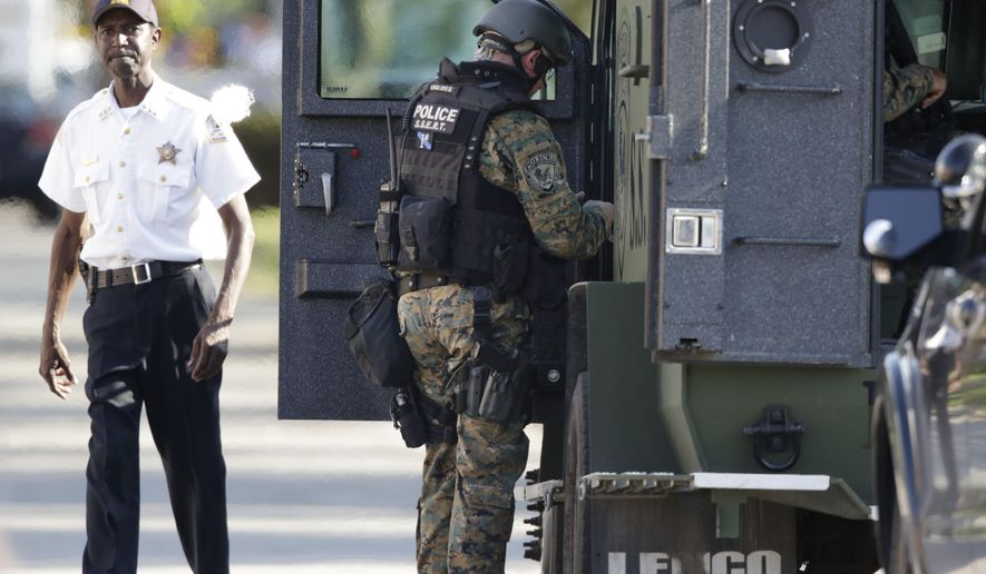 Police don body armor as authorities negotiate with two men who are barricaded in a home and holding a woman and five children hostage in   Harvey, Ill., Tuesday, Aug. 19, 2014, south of Chicago. Officials say two Harvey police officers were wounded by gunfire Tuesday afternoon in the incident after responding to a call about a burglary.(AP Photo/M. Spencer Green)