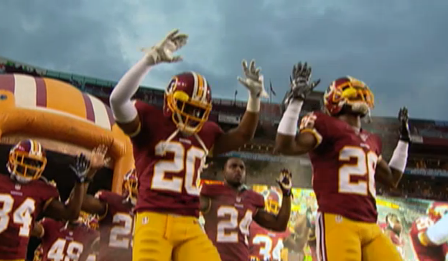 Washington Redskins players put their hands up to show solidarity with Ferguson, Missouri, protesters before a preseason game against the Cleveland Browns on August 18, 2014. (Screengrab from CSNWashington.com)