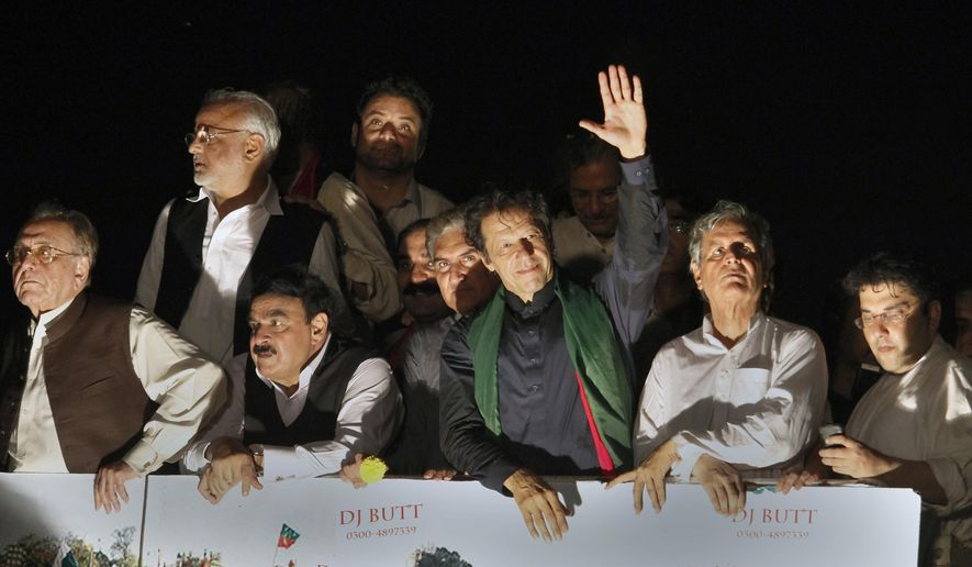 Pakistan's cricketer-turned-politician Imran Khan waves to supporters as he leads a march toward parliament in Islamabad, Pakistan, Wednesday, Aug. 20, 2014.  Tens of thousands of protesters armed with wire cutters and backed by cranes broke through barriers protecting Pakistan's parliament and other government buildings Tuesday night, demanding the country's Prime Minister Nawaz Sharif resign. (AP Photo/Anjum Naveed)