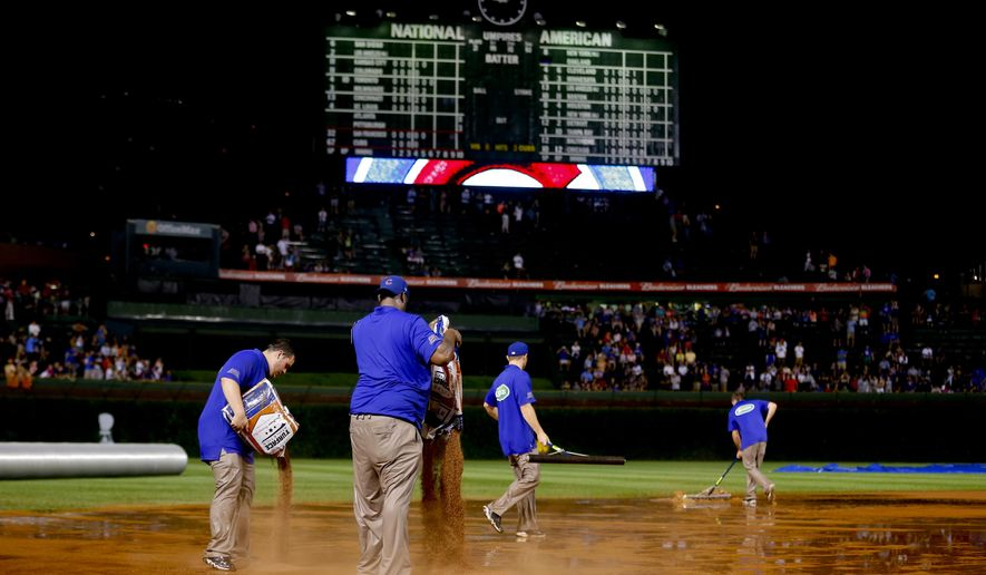 The grounds crew works on the field after a heavy rain soaked Wrigley Field during the fifth inning of a baseball game between the San Francisco Giants and the Chicago Cubs on Tuesday, Aug. 19, 2014, in Chicago. (AP Photo/Jeff Haynes)