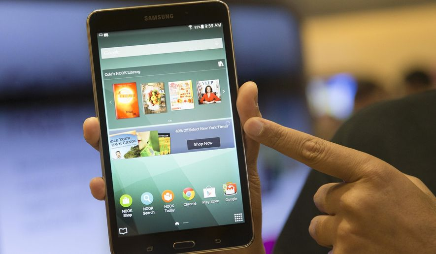 A brand ambassador handles a new Samsung Galaxy Tab 4 Nook during the unveiling of the co-branded tablet that will replace B&N's Nook, Wednesday, Aug. 20, 2014, in New York. The 7-inch tablet will sell for $179 after a $20 instant rebate, the same entry price of the non-branded Samsung Galaxy Tab 4. (AP Photo/John Minchillo)
