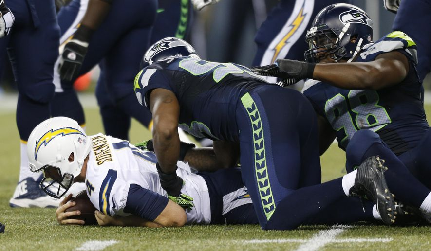 San Diego Chargers quarterback Brad Sorensen, left, is sacked by Seattle Seahawks defensive ends O'Brien Schofield, center, and Greg Scruggs, right, during the second half of a preseason NFL football game, Friday, Aug. 15, 2014, in Seattle. The Seahawks defeated the Chargers 41-14. (AP Photo/John Froschauer)