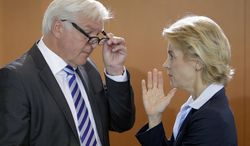 German foreign minister Frank-Walter Steinmeier, left, listens to German defense minister Ursula von der Leyen, as they arrive for the weekly cabinet meeting at the chancellery in Berlin, Germany, Wednesday, Aug. 20, 2014. (AP Photo/Michael Sohn)