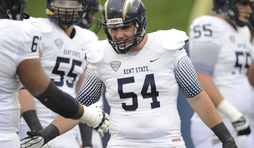 In this undated photo provided by Kent State University, center Jason Bitsko is congratulated during an BCAA football game. Kent State says Bitsko has died and that police believe he passed away from an undetermined medical issue. He was found unresponsive in the bedroom of his off-campus apartment Wednesday, Aug. 20, 2014. (AP Photo/Kent State University)