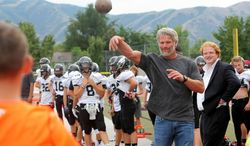In this photo taken on Tuesday, Aug. 19, 2014, former NFL football player Brett Favre plays catch with a few fans prior to talking with the Alta High School football team in Sandy, Utah. (AP Photo/The Deseret News, Scott G Winterton)  SALT LAKE TRIBUNE OUT;  MAGS OUT