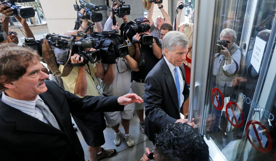 Former Virginia Gov. Bob McDonnell arrives at federal court with his attorney, Henry Asbill (left). After more than three weeks of his trial, Mr. McDonnell took the stand in his own defense Wednesday against charges that he and his wife, Maureen, traded more than $165,000 in gifts and loans for undue access. (Associated Press)