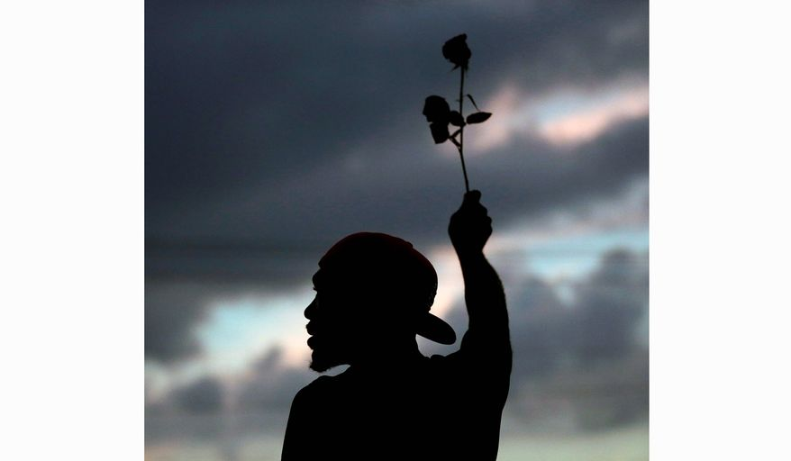 A man holds up a rose during a protest Monday, Aug. 18, 2014, for Michael Brown, who was killed by a police officer Aug. 9 in Ferguson, Mo. Brown's shooting has sparked more than a week of protests, riots and looting in the St. Louis suburb. (AP Photo/Charlie Riedel)