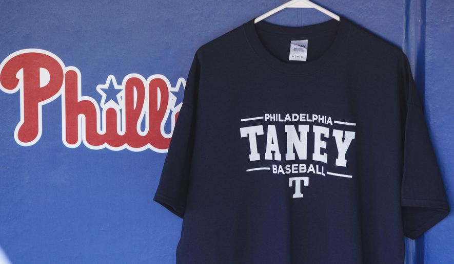 A Taney Dragon t-shirt hangs in the Phillies dugout during the first inning of a baseball game against the Seattle Mariners, Wednesday, Aug. 20, 2014, in Philadelphia. The Taney Youth Little League team from Philadelphia is playing in the Little League World Series. (AP Photo/Chris Szagola)
