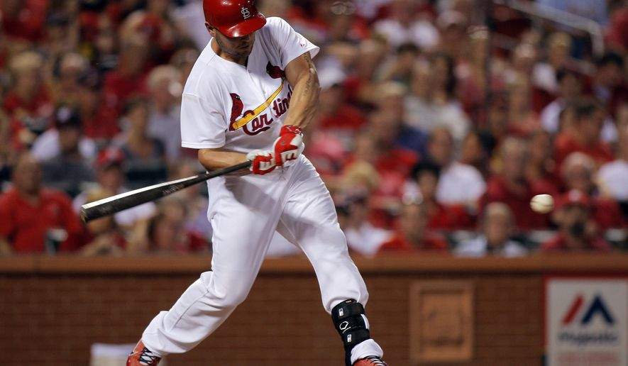 St. Louis Cardinals' Matt Holliday swings for a RBI single during the third inning of a baseball game against the Cincinnati Reds, Tuesday, Aug. 19, 2014, in St. Louis. (AP Photo/Scott Kane)