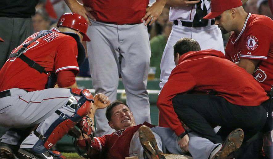 Los Angeles Angels starting pitcher Garrett Richards grimaces as he is attended to on the field after he was injured during the second inning of a baseball game against the Boston Red Sox at Fenway Park in Boston, Wednesday, Aug. 20, 2014. (AP Photo/Elise Amendola)