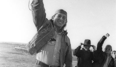 A member of the American Indian Movement (AIM) at Wounded Knee, S.D., March 8, 1973 raises his rifle and cheers after receivign news that federal authorities had extended the cease fire for further negotiations to end the standoff.  AIM was occupying the village that was the site of the 1890 Wounded Knee massacre. (AP Photo)