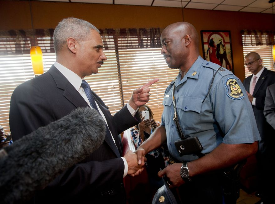 Attorney General Eric Holder talks with Capt. Ron Johnson of the Missouri State Highway Patrol at Drake's Place Restaurant, Wednesday, Aug. 20, 2014, in Florrissant, Mo. Holder arrived in Missouri on Wednesday, as a small group of protesters gathered outside the building where a grand jury could begin hearing evidence to determine whether a Ferguson police officer who shot 18-year-old Michael Brown should be charged in his death. (AP Photo/Pablo Martinez Monsivais, Pool)