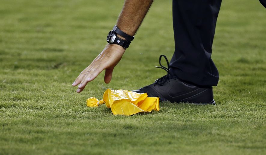 An official picks up a penalty flag off the turf during an NFL preseason football game between the Washington Redskins and the Cleveland Browns Monday, Aug. 18, 2014, in Landover, Md. (AP Photo/Alex Brandon)