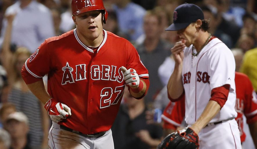 Los Angeles Angels' Mike Trout trots to the dugout after scoring on Josh Hamilton's sacrifice fly as Boston Red Sox starting pitcher Clay Buchholz, right, walks back to the mound in the fifth inning of a baseball game at Fenway Park in Boston, Wednesday, Aug. 20, 2014. (AP Photo/Elise Amendola)