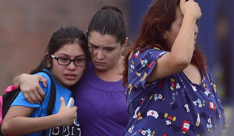 In this photo taken on Tuesday afternoon, Aug. 19, 2014, people react at Picacho Middle School after a lightning strike at a football field near the school in Las Cruces, N.M.  Authorities say a teenage boy is hospitalized in critical condition after being struck by lightning during football practice at Picacho Middle School. (AP Photo/Las Cruces Sun-News,Carlos Javier Sanchez)