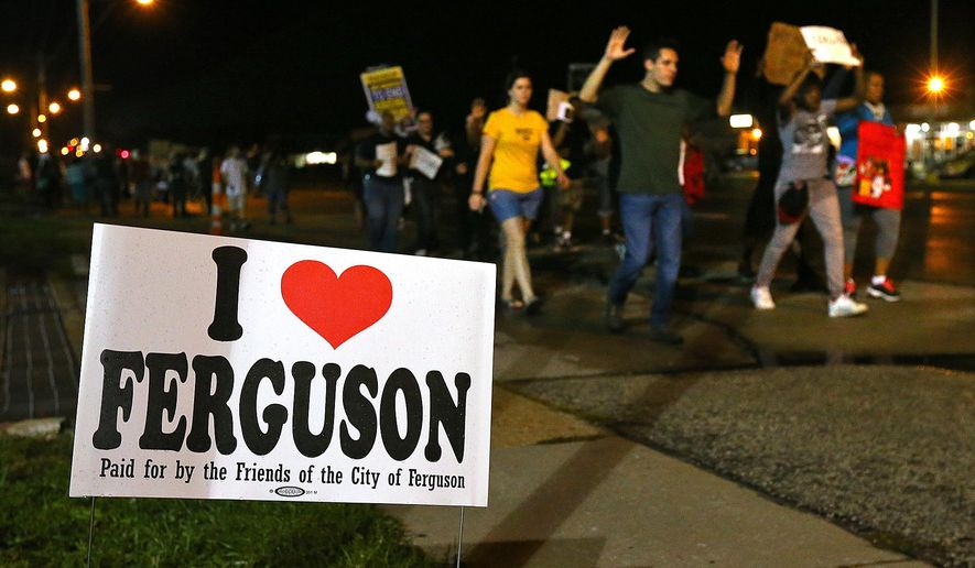 A small group of protesters marches down West Florissant Avenue in Ferguson, Mo. on Wednesday, Aug. 20, 2014. On Aug. 9, 2014, a white police officer fatally shot Michael Brown, an unarmed black 18-year old, in the St. Louis suburb. (AP Photo/Atlanta Journal-Constitution, Curtis Compton)