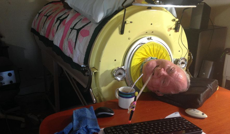 In this Aug. 9, 2014 photo, Paul Alexander uses a plastic stick with a pencil tied to it to type on a keyboard using only his mouth while in his iron lung at his home in Dallas. Alexander is one of 10 people left in the world who still uses an iron lung to breathe. (AP Photo/Courtesy Shelly Conlon, The Waxahachie Daily Light)