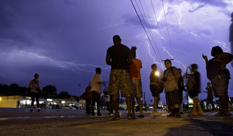 Protesters stand in the street as lightning flashes in the night sky in Ferguson, Mo. on Wednesday, Aug. 20, 2014. A grand jury has begun hearing evidence as it weighs possible charges against the Ferguson police officer who fatally shot 18-year-old Michael Brown. (AP Photo/Jeff Roberson)