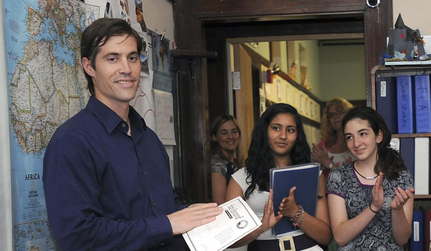 In this June 17, 2011 photo, journalist James Foley receives applause from students at the Christa McAuliffe Regional Charter Public School in Framingham, Mass. Foley had been released a month prior after being detained for six weeks in Libya. Students at the school had written government leaders to work for his release. Foley was abducted in November 2012 while covering the Syrian conflict. Islamic militants posted a video showing his murder on Tuesday, Aug. 19, 2014, and said they killed him because the U.S. had launched airstrikes in northern Iraq. (AP Photo/MetroWest Daily News, Ken McGagh) MANDATORY CREDIT