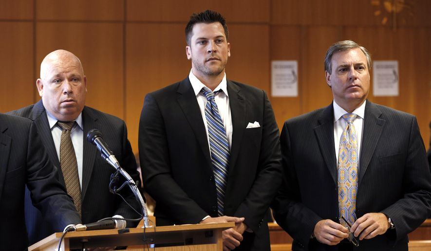 Evan Reed, center, stands with his attorneys Ben Goneck, left, and David Gorcyca during a preliminary hearing on a sexual assault charge Thursday, Aug. 21, 2014, in Detroit. Reed, a Detroit Tigers minor league pitcher, is accused of sexually assaulting a woman at a downtown Detroit hotel. He's charged with third-degree criminal sexual conduct. (AP Photo/Paul Sancya)